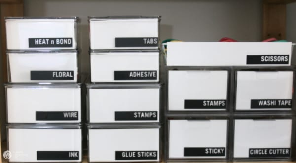 Craft Room Organization containers with black labels.