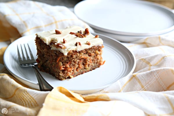 Piece of carrot cake with cream cheese frosting on a white plate.