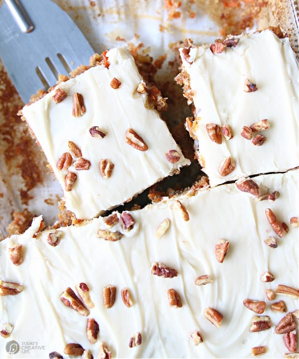 Carrot Cake Recipe with pecan sprinkled on cream cheese frosting in a cake pan being cut and served.