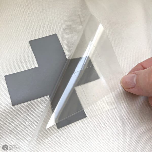 Peeling off iron-on vinyl layer when applying designs to fabric.