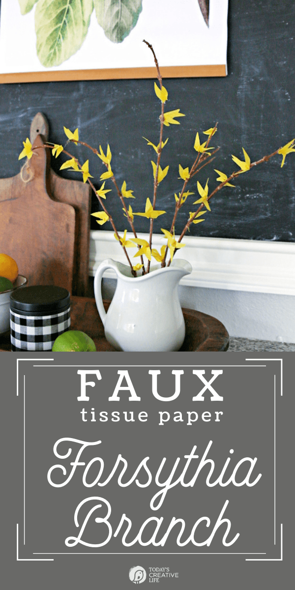 Faux Forsythia Branches made with yellow tissue paper, displayed in a white ceramic pitcher.