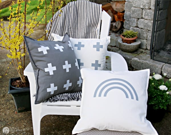 White chair with 3 decorative pillows in grey and white.