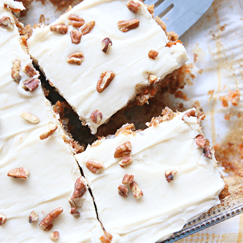 Carrot cake sliced up in squares in a cake pan.