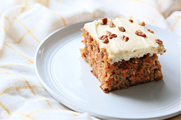 Carrot cake with frosting served on a white plate