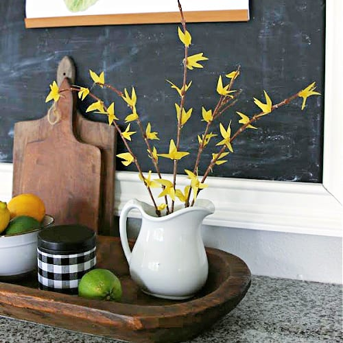 white pitcher filled with faux tissue paper forsythia branches