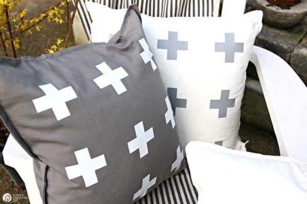 DIY Patio Ideas with pillows. One grey pillow with white designs. One white pillow with grey designs. Cricut Maker Iron-on Ideas