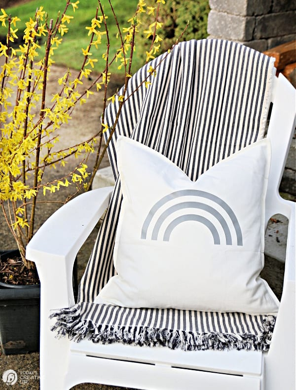 White chair with striped blanket and white rainbow pillow for DIY Patio Ideas. Cricut Maker Iron-on project.