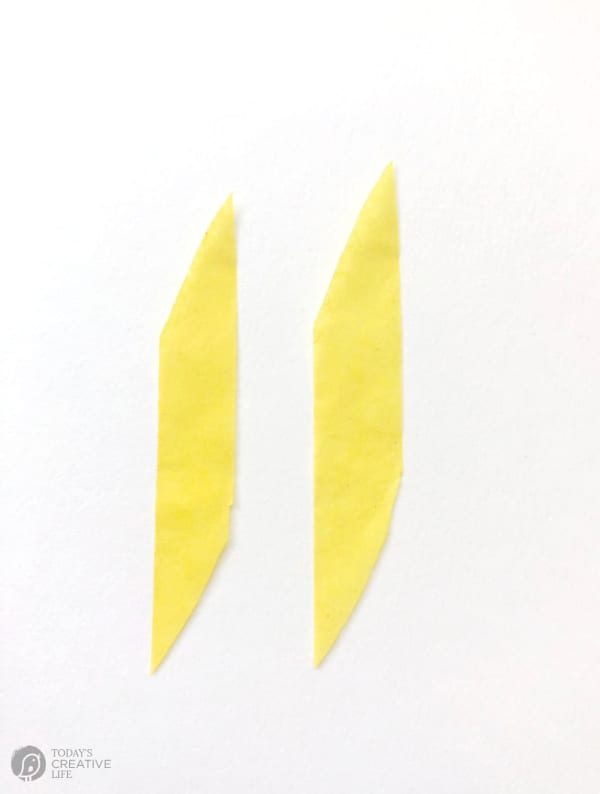 Two small strips of yellow tissue paper for making faux forsythia blooms.