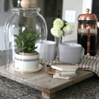 Wood tray on kitchen counter styled with coffee supplies.