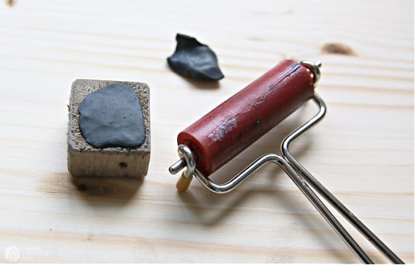 Black Sugru moldable glue spread over a cube of wood to be used for a tray leg.