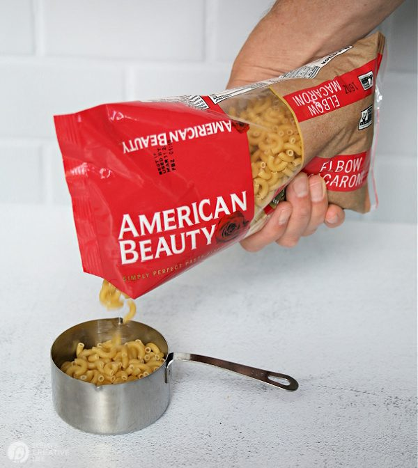 Pouring pasta into measuring cup.