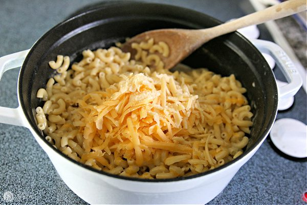 Adding shredded cheese to boiled pasta for homemade mac and cheese